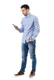 Zijaanzicht van het jonge slimme toevallige bericht van de bedrijfsmensenlezing op celtelefoon Stock Afbeeldingen