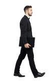Zijaanzicht van het jonge uitvoerende het dragen laptop lopen Royalty-vrije Stock Foto