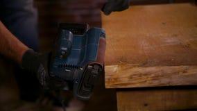 Zijaanzicht van het oppoetsen van houten randen met molen in arbeidershanden stock video