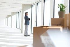 Zijaanzicht van het rijpe zakenman kijken door venster in nieuw bureau Royalty-vrije Stock Foto
