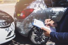 Zijaanzicht van het schrijven op klembord terwijl verzekeringsagent die auto na ongeval onderzoeken royalty-vrije stock fotografie