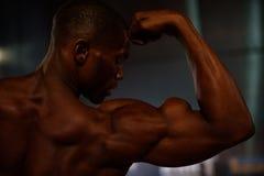Zijaanzicht van het zwarte Afrikaanse Amerikaanse close-up van geschiktheids model tonende spieren op studioachtergrond stock fotografie