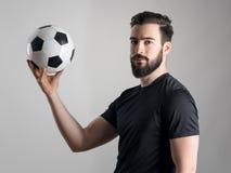 Zijaanzicht van intens schaduwportret van de bal van de voetballerholding Stock Foto