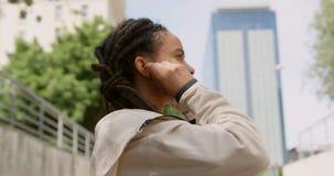 Zijaanzicht van jonge Afrikaanse Amerikaanse vrouw die oortelefoons in de stad 4k dragen stock footage
