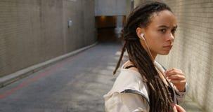 Zijaanzicht van jonge Afrikaanse Amerikaanse vrouw die oortelefoons in de stad 4k dragen stock videobeelden