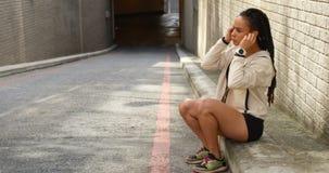 Zijaanzicht van jonge Afrikaanse Amerikaanse vrouw die oortelefoons in de stad 4k dragen stock video