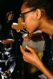 Zijaanzicht van jonge barista die geroosterde koffiebonen ruiken Stock Foto