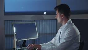 Zijaanzicht van jonge elektronikaingenieur die met zijn onderzoek naar computer belast Het professionele Schrijven bij de Program stock video