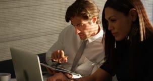 Zijaanzicht van jonge Kaukasische bureaustafmedewerkers die aan laptop bij bureau in een modern bureau 4k werken stock video
