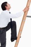 Zijaanzicht van jonge kleinhandelaar die een ladder beklimt Stock Afbeeldingen