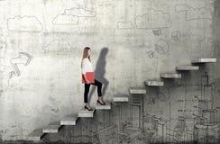 Zijaanzicht van jonge onderneemster die de treden met bedrijfsschets op concrete achtergrond beklimmen stock foto