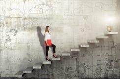 Zijaanzicht van jonge onderneemster die de treden met ideelamp beklimmen op concrete achtergrond stock foto