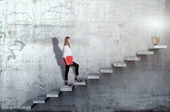 Zijaanzicht van jonge onderneemster die de treden met ideelamp beklimmen op concrete achtergrond stock foto's