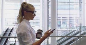 Zijaanzicht van Kaukasische onderneemster gebruikend mobiele telefoon en drinkend koffie in de hal op kantoor 4 stock videobeelden