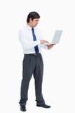Zijaanzicht van kleinhandelaar die aan zijn laptop werkt Royalty-vrije Stock Foto's