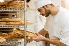 zijaanzicht van knappe bakker die vers brood op plank zetten stock foto