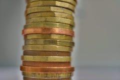 Zijaanzicht van lange stapel van metaalmuntstukken in gouden en koperkleur voor zilveren achtergrond Royalty-vrije Stock Afbeelding