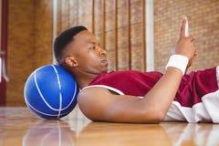 Zijaanzicht van mannelijke basketbalspeler die mobiele telefoon met behulp van Royalty-vrije Stock Afbeeldingen