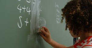 Zijaanzicht van mengen-rasschoolmeisje die groen bord in klaslokaal schoonmaken op school 4k stock footage