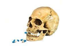 Zijaanzicht van menselijke schedel met pil in tanden Stock Foto