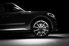 Zijaanzicht van moderne zwarte SUV-auto in een schijnwerper Stock Fotografie