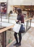 Zijaanzicht van modieuze aantrekkelijke vrouw status in binnenland van het winkelcomplex met het winkelen zakken stock foto's