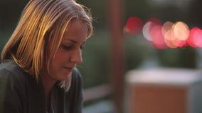 Zijaanzicht van mooie jonge vrouwenzitting in koffie en het onderzoeken van de afstand Close-up, vage lichten, stedelijke straat stock videobeelden