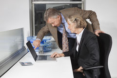 Zijaanzicht van onderneemster en de mens die laptop het scherm bij bureau in bureau bekijken Royalty-vrije Stock Afbeelding