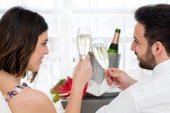 Zijaanzicht van paar het vieren met mousserende wijn stock fotografie