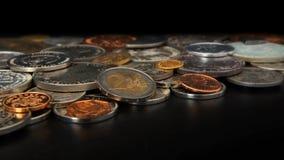 Zijaanzicht van partij van muntstukken van verschillende landen van de wereld wanordelijk op zwarte lijst Nadruk op 2 euromuntstu stock foto