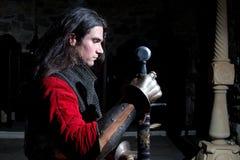 Zijaanzicht van Ridder With Sword Looking neer tegen Zwarte Achtergrond Royalty-vrije Stock Foto's