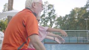 Zijaanzicht van rijpe man, vrouwen en meisjezitting op de rand van het pool bespattende water met handen grootmoeder stock video