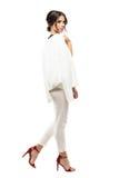 Zijaanzicht van schitterende elegante bedrijfsvrouw in wit kostuum die en camera lopen bekijken royalty-vrije stock foto's
