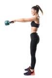 Zijaanzicht van sterke sportieve geschiktheidsvrouw die 12 kg kettlebell in medio luchtmotie slingeren Stock Foto's