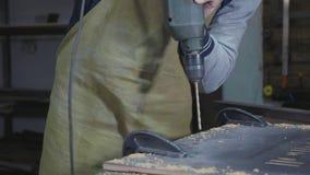 Zijaanzicht van timmerman die een houten plank, close-up langzame motie boren stock footage