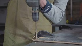 Zijaanzicht van timmerman die een houten plank, close-up langzame motie boren stock video