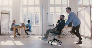 Zijaanzicht van twee gekke pret mannelijke bedrijfsmensen wordt geschoten die bureaustoel langs grote open plekzaal berijden, vie stock videobeelden