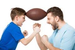 Zijaanzicht van vader met zoon die en rugbybal tussen gezichten gillen houden stock afbeeldingen