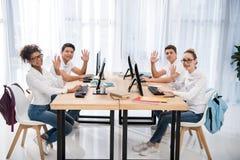 zijaanzicht van vier jonge multiculturele studenten die camera bekijken stock foto's