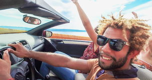 Zijaanzicht van vrienden die wapens golven die op gesorteerd kustweg in convertibel drijven, stock video