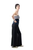 Zijaanzicht van in vrouw in breed-beenbroek en van-de-schouder het hoogste stellen bij camera royalty-vrije stock foto's