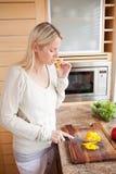 Zijaanzicht van vrouw het knagen aan terwijl het snijden van groenten Royalty-vrije Stock Foto's