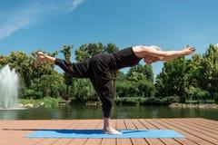 zijaanzicht van vrouw het praktizeren yoga in Strijder III stock fotografie