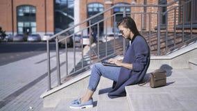 Zijaanzicht van vrouw met laptop op treden in de straat stock videobeelden