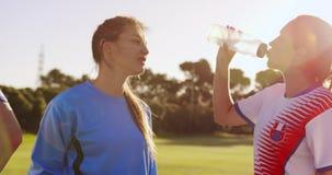 Zijaanzicht van vrouwelijk voetballers drinkwater 4k stock video