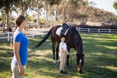 Zijaanzicht van vrouwelijke jockey die zuster status door paard bekijken royalty-vrije stock foto's