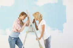 Zijaanzicht van vrouwelijke vrienden die samen in nieuw huis schilderen royalty-vrije stock fotografie
