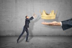 Zijaanzicht van weinig zakenman die uit voor gouden kroon bereiken die boven grote man hand te voorschijn komend uit recht wordt  royalty-vrije stock foto's