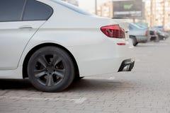 Zijaanzicht van witte auto die op bedekt parkeerterreingebied wordt geparkeerd op de vage achtergrond van de voorstadweg op helde royalty-vrije stock afbeeldingen