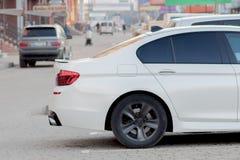 Zijaanzicht van witte auto die op bedekt parkeerterreingebied wordt geparkeerd op de vage achtergrond van de voorstadweg op helde stock foto's